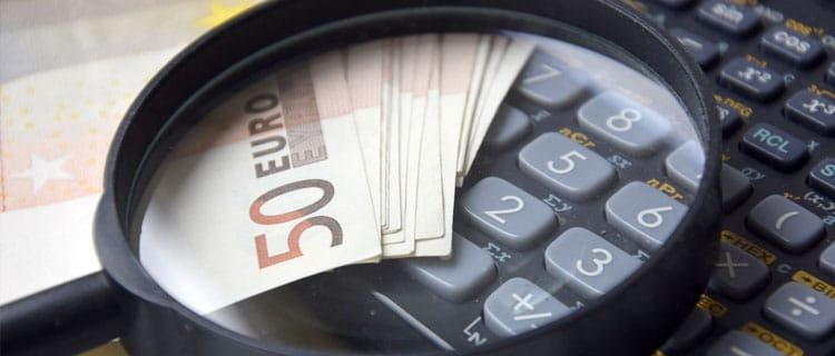 Calculadora, dinero y lupa en 7 Desafíos y trucos para ahorrar si tu presupuesto es bajo