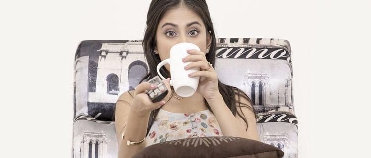 Chica tomando café frente a la tele con mando a distancia. Por qué no me gustan los reality shows